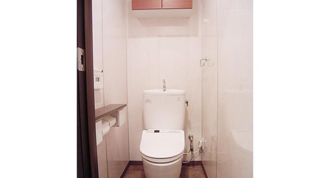 リフォーム後のトイレ。壁材は掃除のしやすいパネル材に、上部には雰囲気を合わせた収納を設けました。